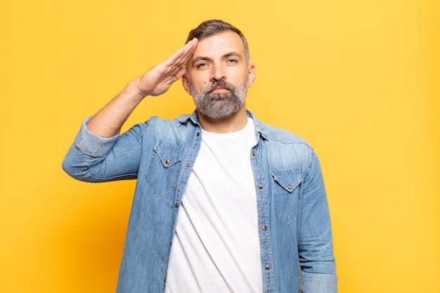 존경을 보여주는 명예와 애국심의 행위에 군사 인사로 인사하는 성인 잘 생긴 남자 프리미엄 사진