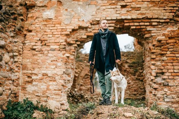 ヨーロッパの城のレンガの壁を越えて屋外かわいいかわいいハスキー子犬犬と一緒に歩いているビジネス服で大人のハンサムな男が残っています。