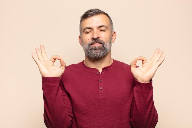 Взрослый красивый мужчина выглядит сосредоточенным и медитирует, чувствует удовлетворение и расслабление, думает или делает выбор