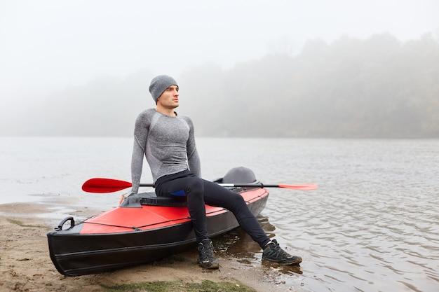 Взрослый красавец сидит на лодке и смотрит вдаль с мечтательным выражением лица, одетый в спортивную одежду, позирует на туманной реке