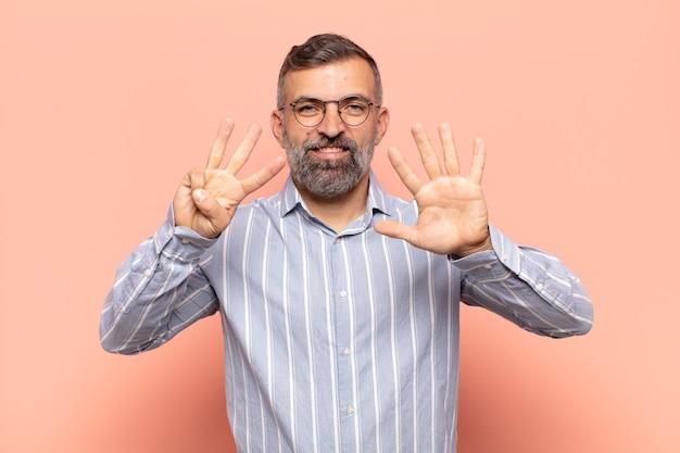 笑顔でフレンドリーに見える大人のハンサムな男、前に手を前に8または8を示し、カウントダウン