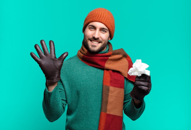 笑顔でフレンドリーに見える大人のハンサムな男は、前に手を前に、カウントダウンして、5番または5番を示しています。病気と寒さの概念