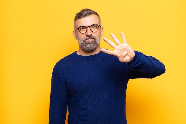 Взрослый красивый мужчина улыбается и выглядит дружелюбно, показывает номер четыре или четвертый с рукой вперед, отсчитывая
