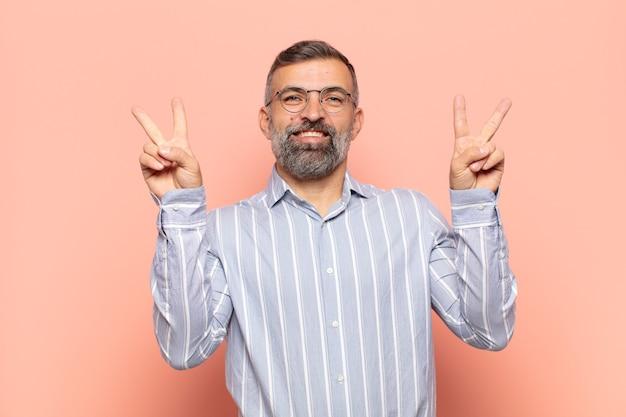 Взрослый красивый мужчина улыбается и выглядит счастливым, дружелюбным и довольным, жестикулирует победу или мир обеими руками