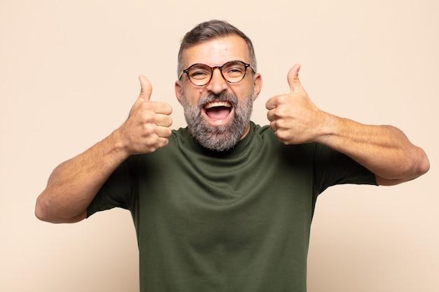두 엄지 손가락으로 광범위하게 행복하고 긍정적이며 자신감 있고 성공적인 웃는 성인 잘 생긴 남자