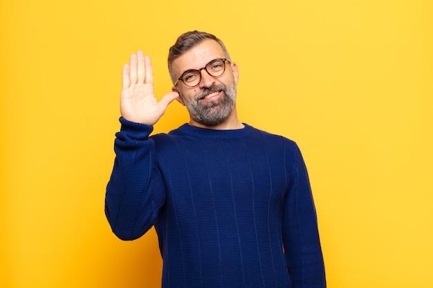 幸せにそして元気に笑って、手を振って、あなたを歓迎して挨拶するか、さようならを言う大人のハンサムな男