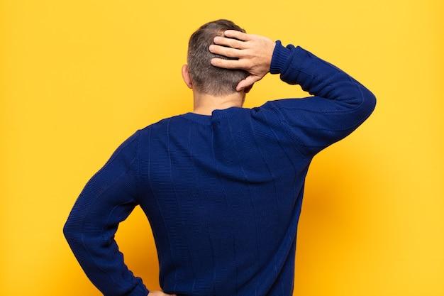 考えたり疑ったり、頭を掻いたり、困惑したり混乱したりする大人のハンサムな男、背面図または背面図