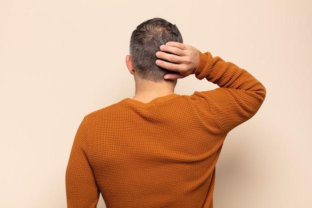 大人のハンサムな男が考えたり疑ったり、頭を掻いたり、困惑したり混乱したり、背面図または背面図