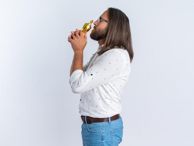 프로필 보기에 안경을 쓴 성인 잘생긴 남자는 복사 공간이 있는 흰색 벽에 격리된 닫힌 눈으로 입 근처에 우승컵을 들고 서 있습니다.