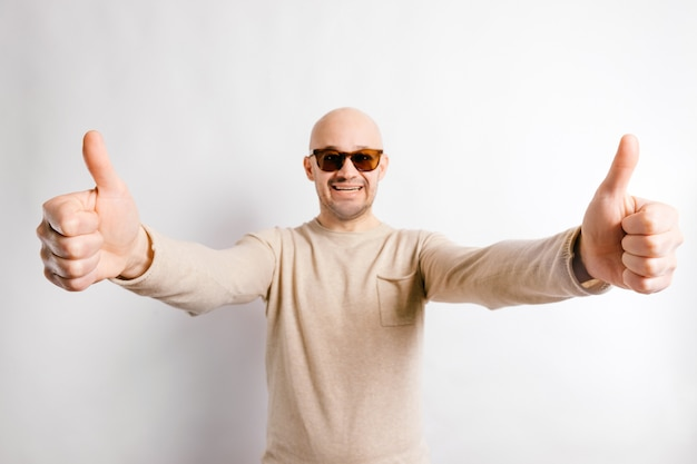 Adult  happy businessman in sunglasses showing thumbs up.