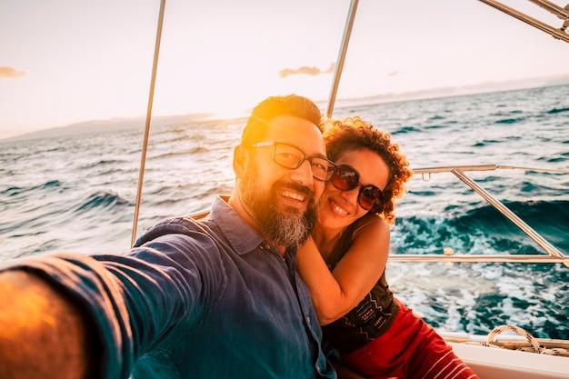 성인 행복한 커플은 바다에서 일몰을 즐기는 보트에서 셀카 요트를