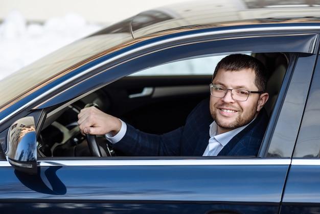 Взрослый счастливый человек бизнесмен за рулем автомобиля