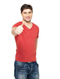白い壁に隔離されたカジュアルで親指を立てるジェスチャーで大人の幸せな男。