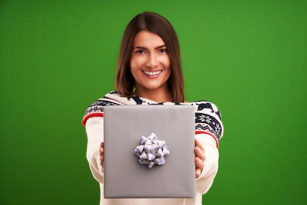 緑の背景の上のクリスマス プレゼントを持つ大人の幸せな女