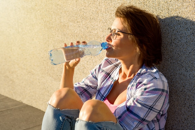 Adult healthy woman drinks water from bottle.