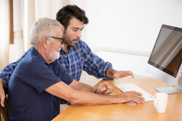 An adult hipster son and senior father spend time together at home, talking, take care father and using computer.