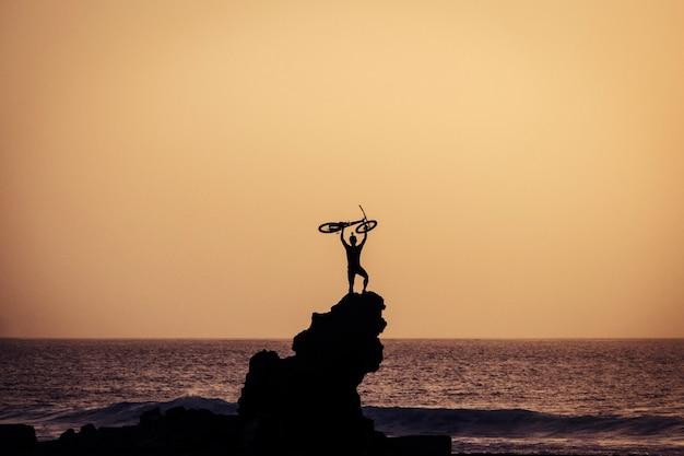 Взрослый держит на руках велосипед на пляже на большой скале - концепция свободы и образ жизни - великолепный закат - океан и море с волнами на заднем плане