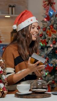 Взрослый держит подарок на видеозвонке на праздничной кухне