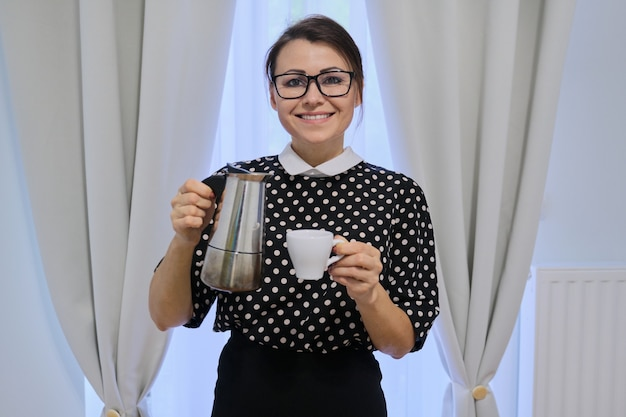 Взрослая домохозяйка держит кофейник и чашку, стоя у окна с шторами