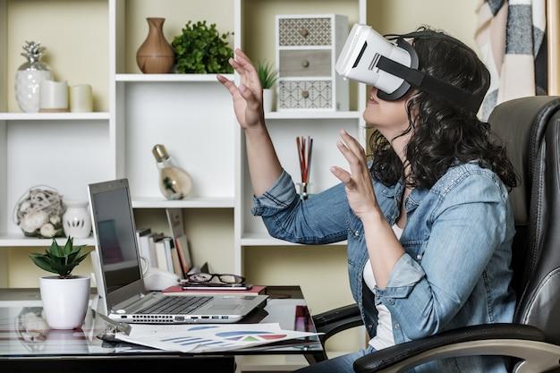 Взрослая женщина погружается, используя очки виртуальной реальности, сидя за столом с нетбуком дома