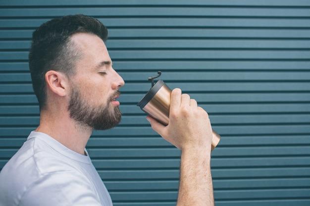 Взрослый стоит и готов выпить горячий напиток из термоса. он закрыл глаза. изолированные на полосатый
