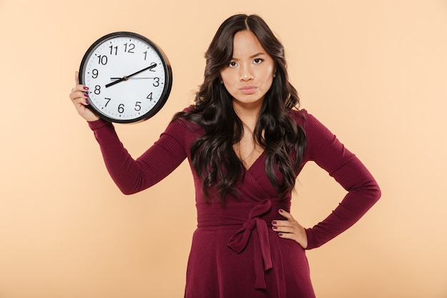 Adult lady with curly long hair holding clock with time after 8 showing anger with facial expressions putting hand on waist over beige background