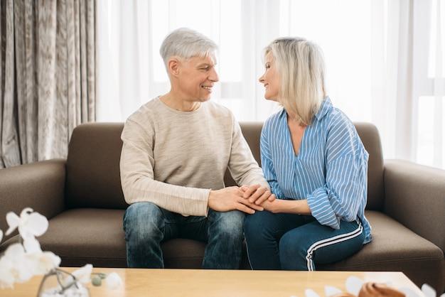 Взрослая любовная пара смотрит друг другу в глаза дома. зрелые муж и жена сидят на диване и обнимаются, счастливая семья