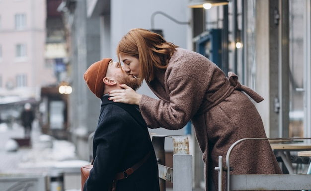 Adult loving couple kissing on a street