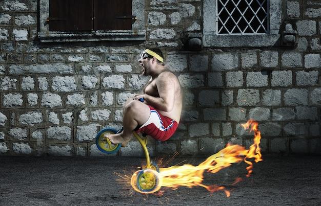 子供の自転車で通りをサイクリングする大人の狂人