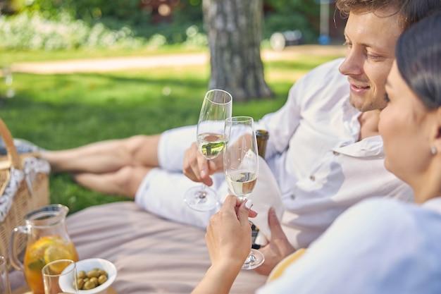 야외에서 함께 이야기하는 동안 손에 차가운 샴페인 잔을 가진 성인 남성과 여성