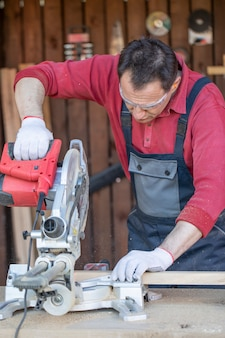 An adult male artisan cuts a wooden plank with a circular saw.