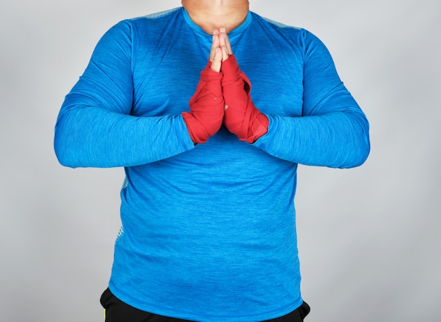 Adult male athlete in blue uniform is in prayer pose