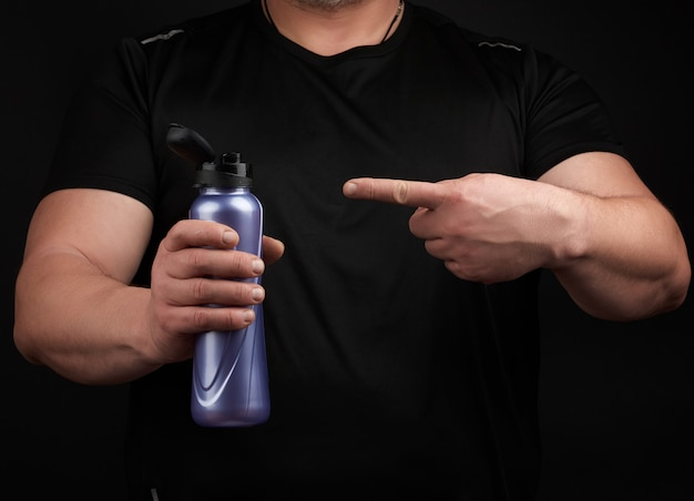 Adult male athlete with muscles holds a plastic bottle of water