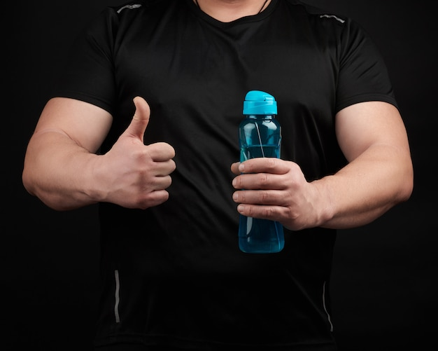 Adult male athlete with muscles holds a plastic water bottle, with his right hand he shows a gesture like