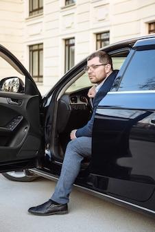 街の通りのシーンで車とメガネで大人の男性実業家
