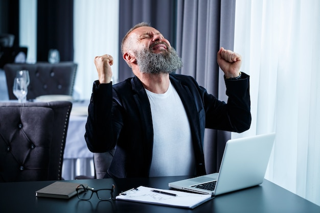 An adult male businessman is working on a new project and looking at the stock growth charts. sits at the table by the large window. looks at the laptop screen and smiles
