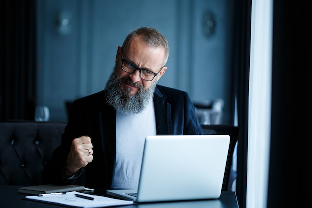 An adult male businessman is working on a new project and looking at the stock growth charts. sits at the table by the large window. looks at laptop screen