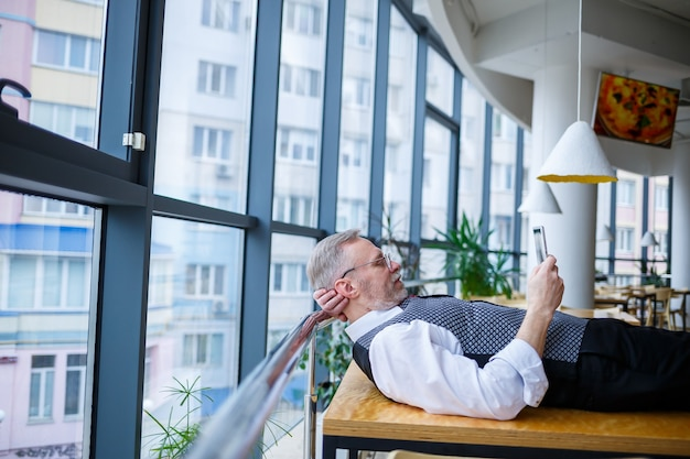 Adult male businessman resting and looking at a tablet in search of ideas for a project to develop new technologies