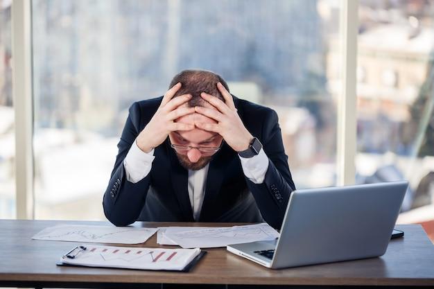 성인 남성 사업가, 교사, 멘토가 사무실에서 새로운 프로젝트를 진행하고 있으며 긴장하고 있습니다. 큰 창가 쪽 테이블에 앉는다. 그는 노트북, 비즈니스 문제에서 일합니다