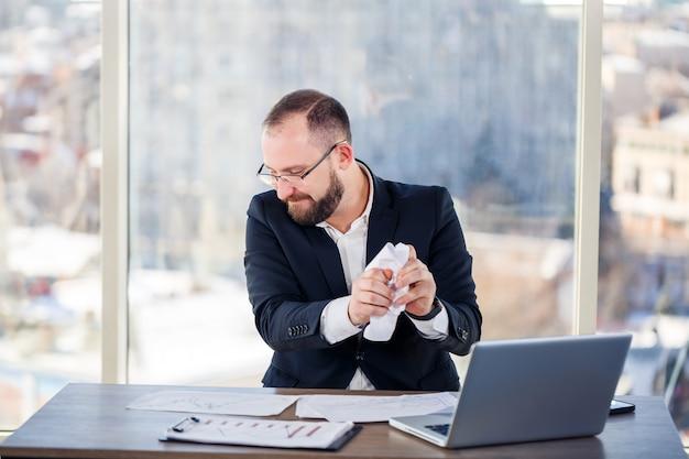 Взрослый мужчина, бизнесмен, учитель, наставник работает над новым проектом в офисе и нервничает. сидит за столом у большого окна. он работает на ноуте, бизнес-проблемы