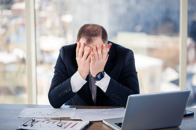 성인 남성 사업가, 교사, 멘토가 사무실에서 새로운 프로젝트를 진행 중이며 긴장합니다. 큰 창가의 테이블에 앉습니다. 그는 노트북, 비즈니스 문제에서 일합니다