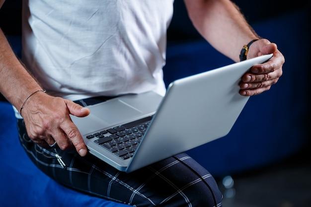 Взрослый мужчина-бизнесмен, учитель, наставник работает над новым проектом. сидит у большого окна на столе. он смотрит на экран ноутбука.