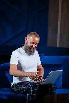 新しいプロジェクトに取り組んでいる成人男性のビジネスマン、教師、メンター。テーブルの上の大きな窓のそばに座っています。彼はノートパソコンの画面を見ています。