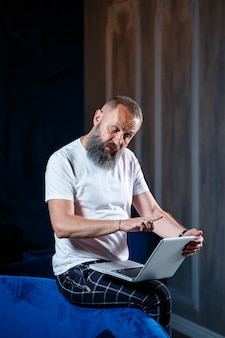 성인 남성 사업가, 교사, 멘토가 새로운 프로젝트를 진행하고 있습니다. 테이블의 큰 창가에 앉습니다. 그는 노트북 화면을 본다.