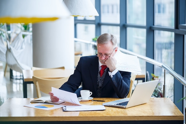 Adult male businessman working on a new project and looking at stock growth charts. sits at a large window at the table. looks at the laptop screen and drinks coffee.