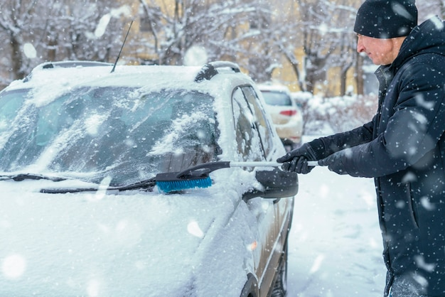 Adult male clean car windshield from snow in blizzard