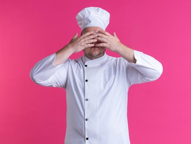 ピンクの壁に隔離された目の前で手を保つシェフの制服と眼鏡を身に着けている大人の男性料理人