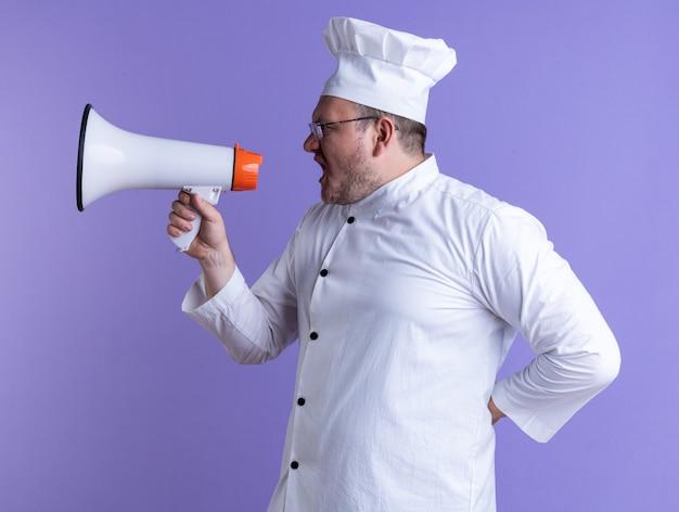 Cuoco maschio adulto che indossa l'uniforme da chef e occhiali in piedi in vista di profilo tenendo la mano dietro la schiena guardando a lato parlando dall'altoparlante isolato su parete viola