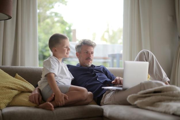 彼の息子と一緒にソファに横になって、ライトの下でラップトップを使用して大人の男性