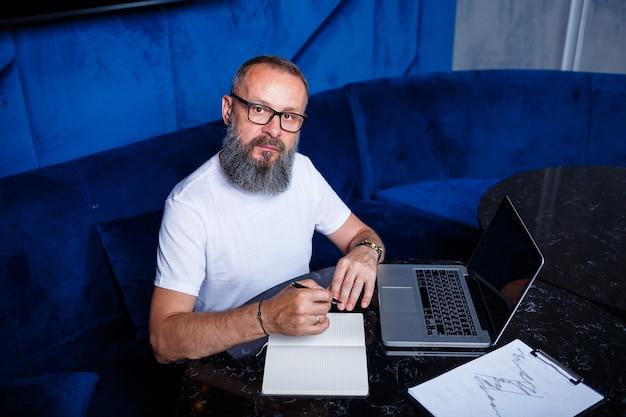 成人男性のメンター、ディレクター、眼鏡をかけたビジネスマン、テーブルに座って書類を勉強するスーツ。就業日のコンセプト